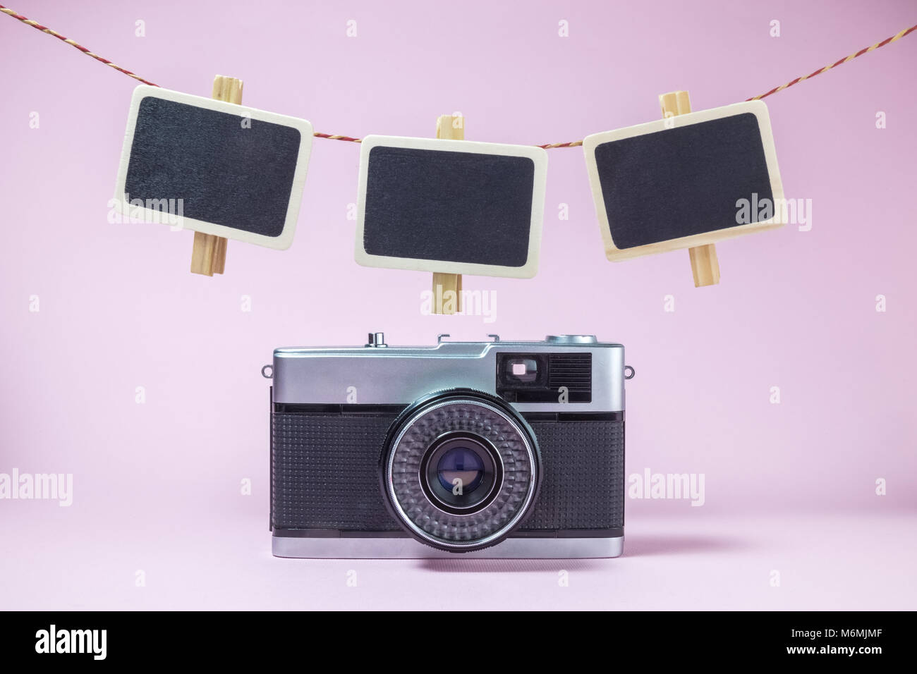 Retro camera and clothespins with blank photo frames on rope minimal ...