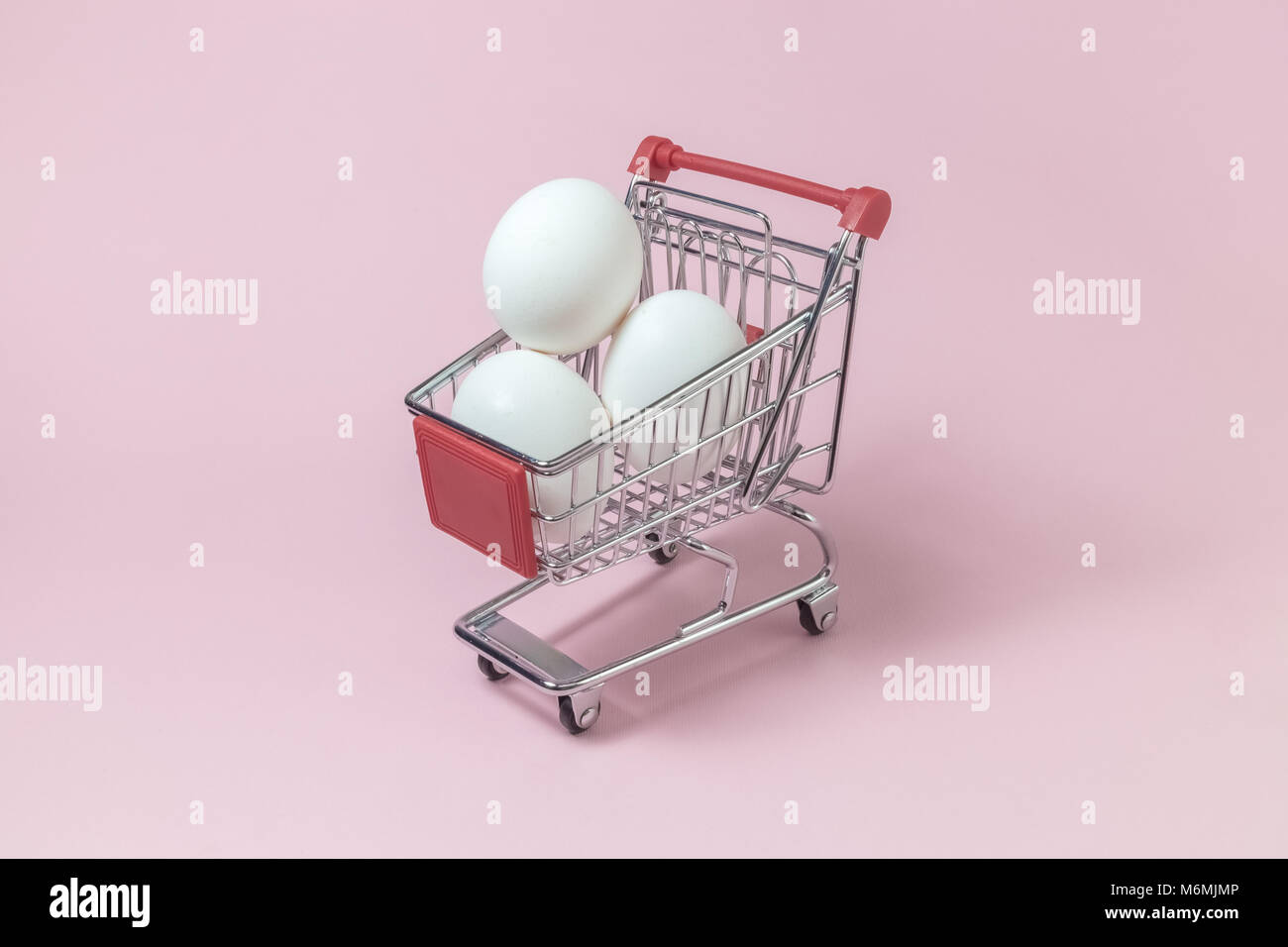 Shopping trolley model full of white eggs against pastel pink rose background minimal concept. Space for copy. - Stock Image