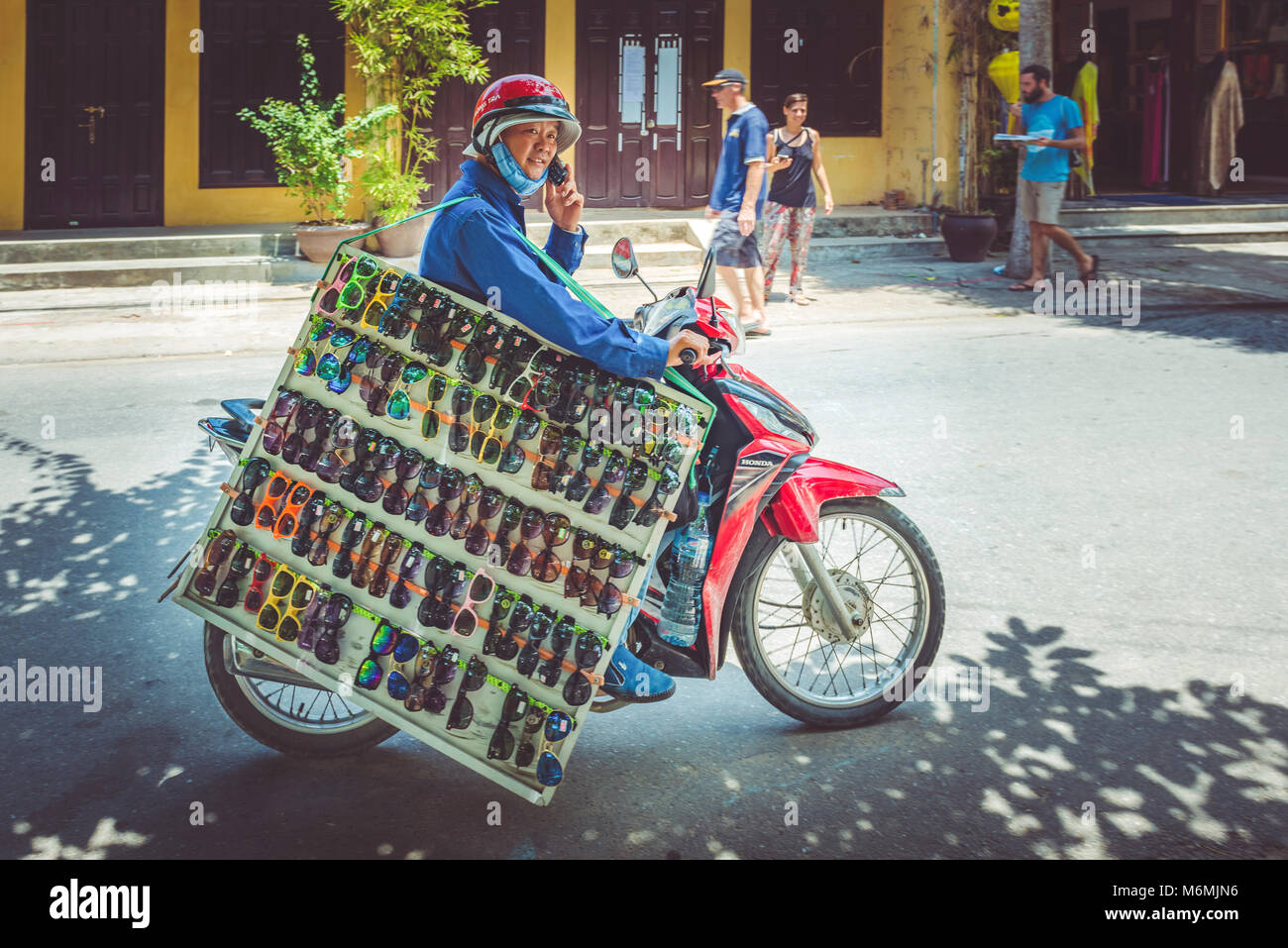 A trader a large board of sunglasses on a moped on the street in Hoi An, Vietnam - Stock Image