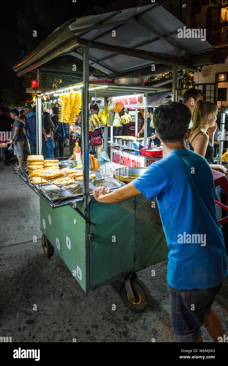 A vendor selling Vietnamese street food from a cart at the night market in Hoi An - Stock Image