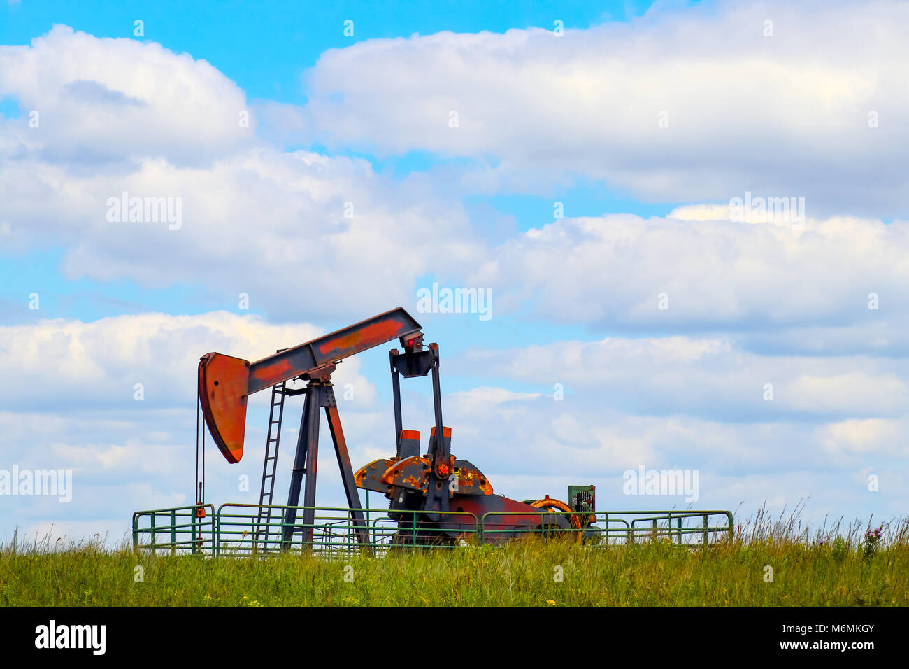Colorful pump jack on oil well - low horizon on prairie with green grass and wild flowers - big blue cloudy sky - room for text Stock Photo