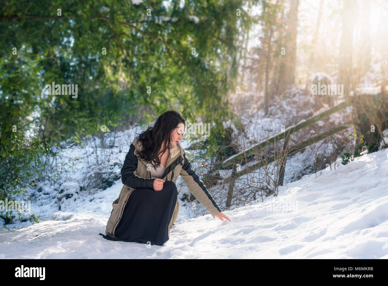 Young brunette woman, dressed in a winter jacket and  black skirt, in a squat position, reaching for snow, on a Stock Photo