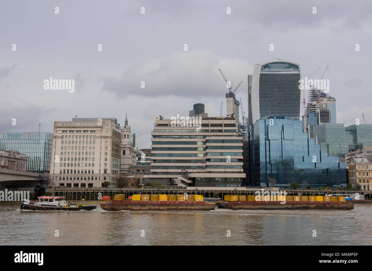 A tug boat on the river thames in central london passing the iconic buildings of the square mile financial district - Stock Image