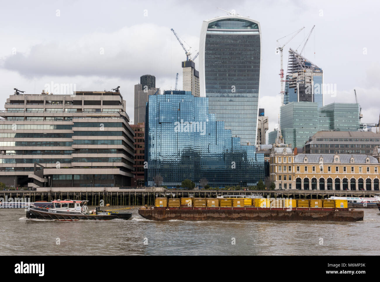 a tug boat towing containers full of london's waste and rubbish along the river thames in the centre of the - Stock Image