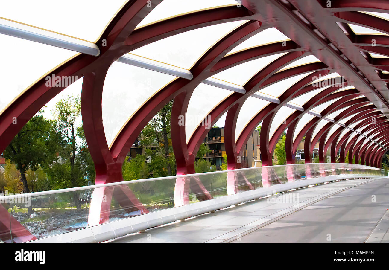The red Peace Bridge crosses the Bow river between the district of Sunnyside and Downtown Calgary, Alberta, Canada. - Stock Image