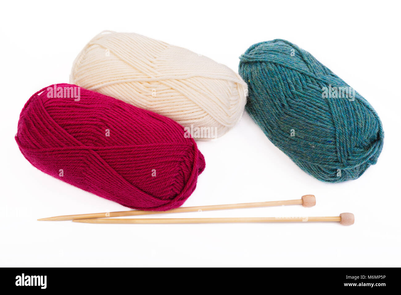 Balls of yarn and wooden knitting needles on white. - Stock Image