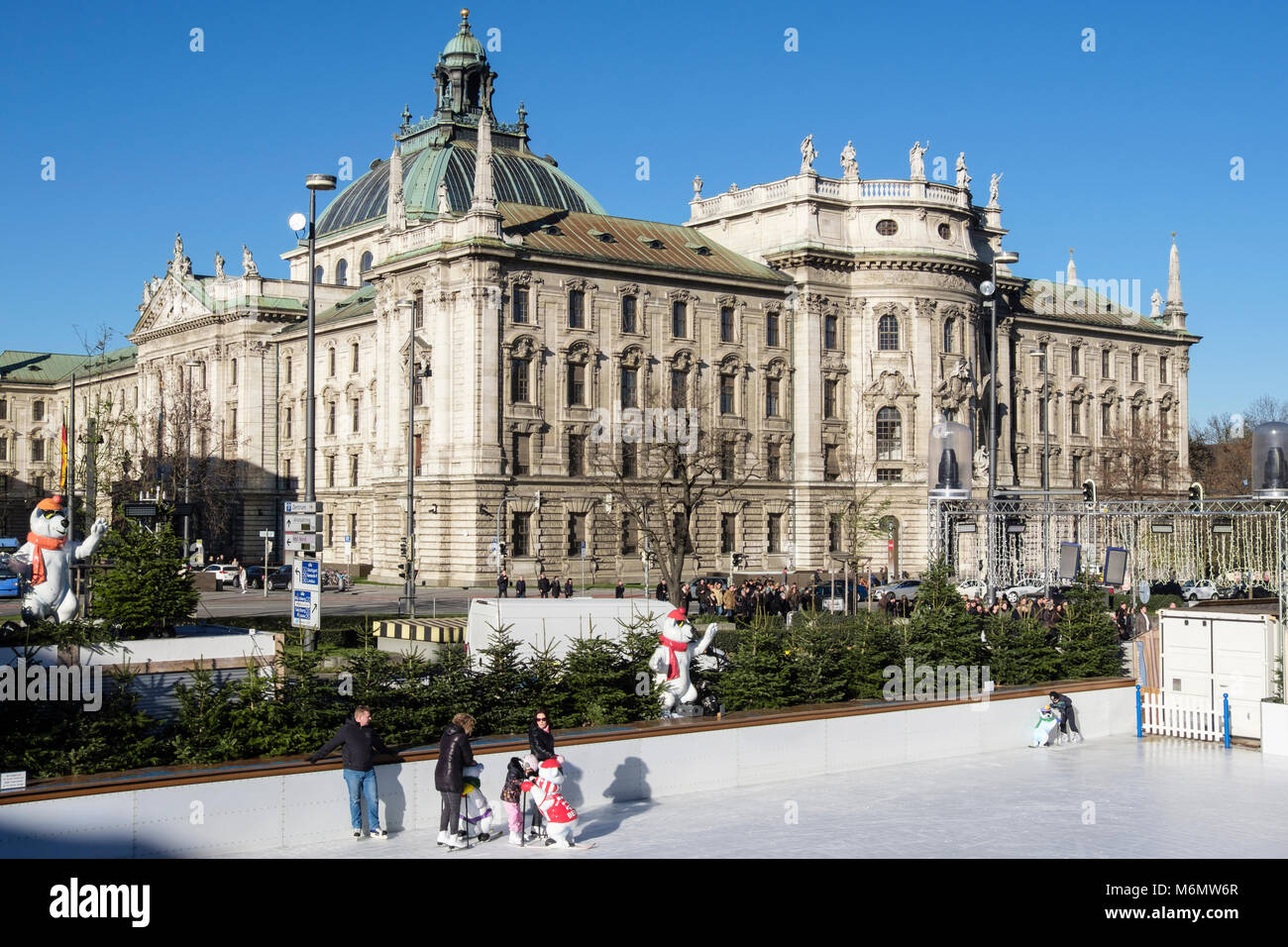 People ice skate on a public Ice skating rink with Justizpalast Munich Palace of Justice behind. Stachus Karlsplatz, - Stock Image