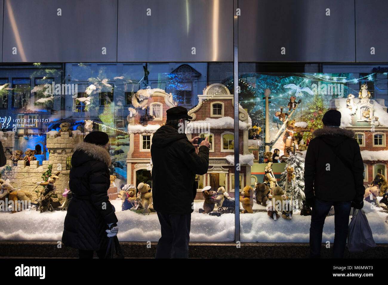 People looking at a christmas display winter scene in department store Galeria Kaufhof shop window. Munich, Bavaria, - Stock Image