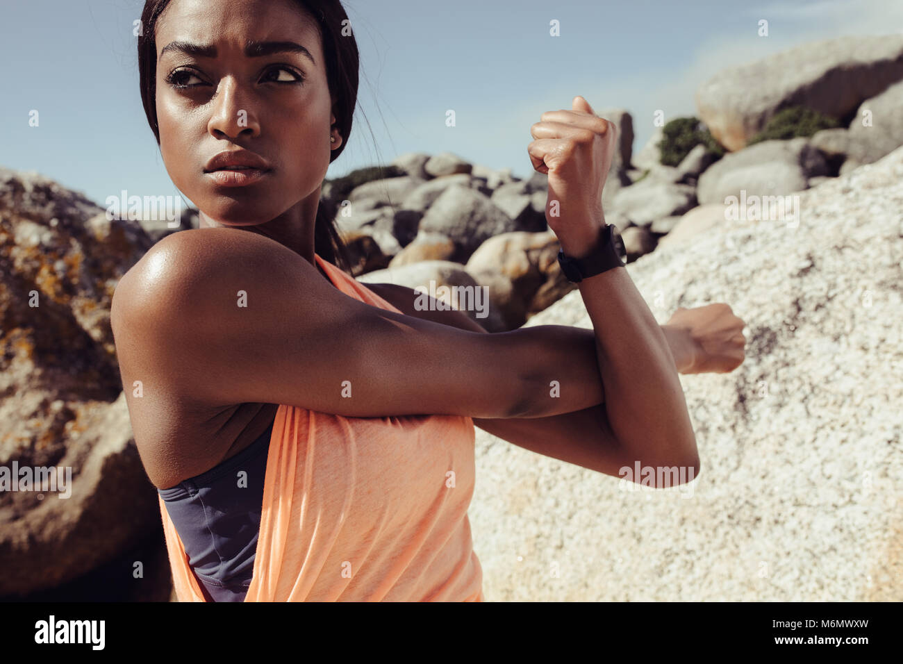 African woman stretching arms at the beach. Fitness female doing warmup workout and looking away outdoors. Closeup - Stock Image