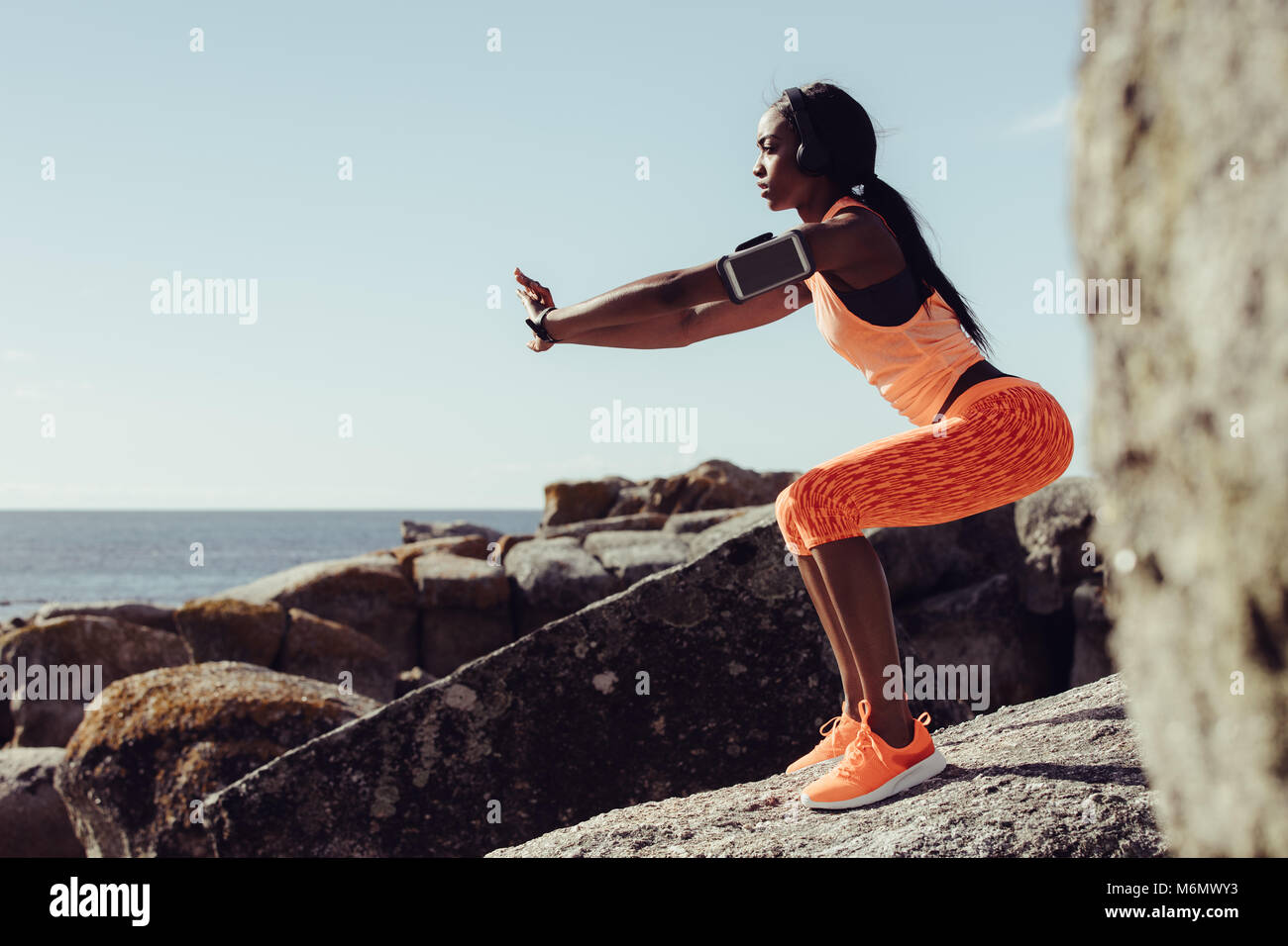 Woman runner doing stretching exercises. Woman doing warm up stretches on rocks at the beach. - Stock Image