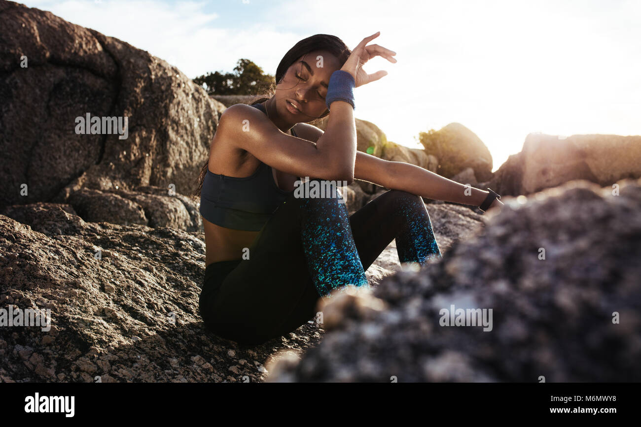 Tired woman sitting and resting after workout on rocks. Woman feeling exhausted after training session. Stock Photo