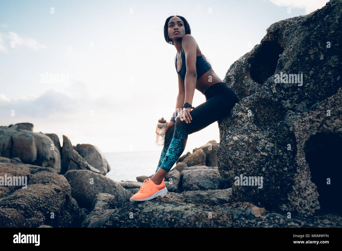 Healthy african woman with a water bottle sitting over a rock. Female relaxing after exercising outdoors. - Stock Image