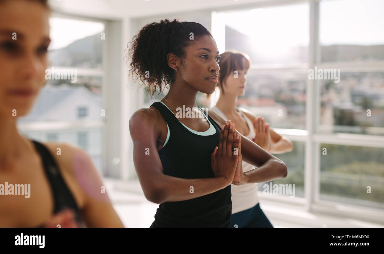 Women stretching and practices yoga in class. Healthy female doing yoga workout in fitness studio. Standing with - Stock Image