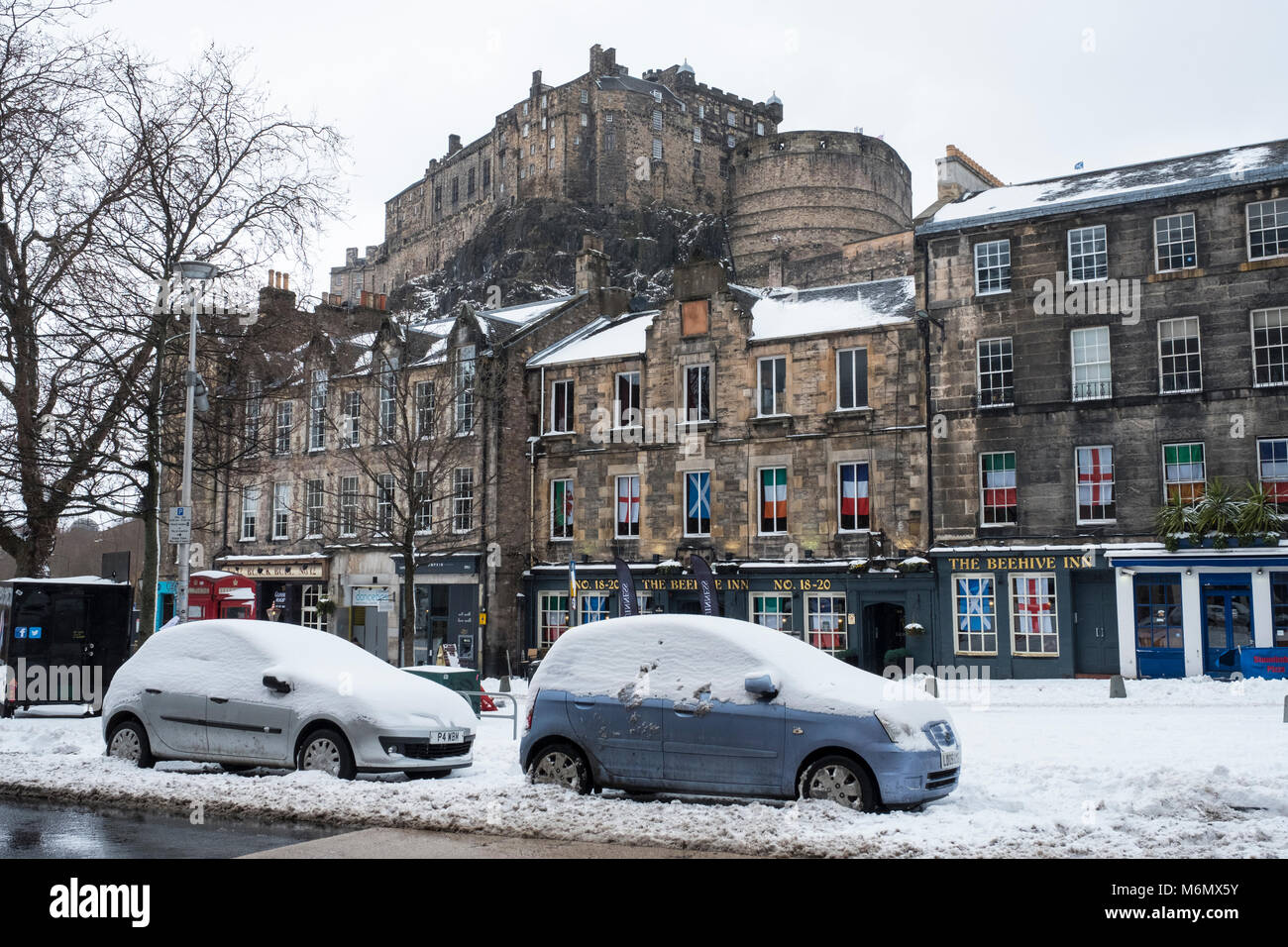 View of Edinburgh Castle and historic old houses from the Grassmarket during heavy snow fall in Edinburgh , Scotland, - Stock Image
