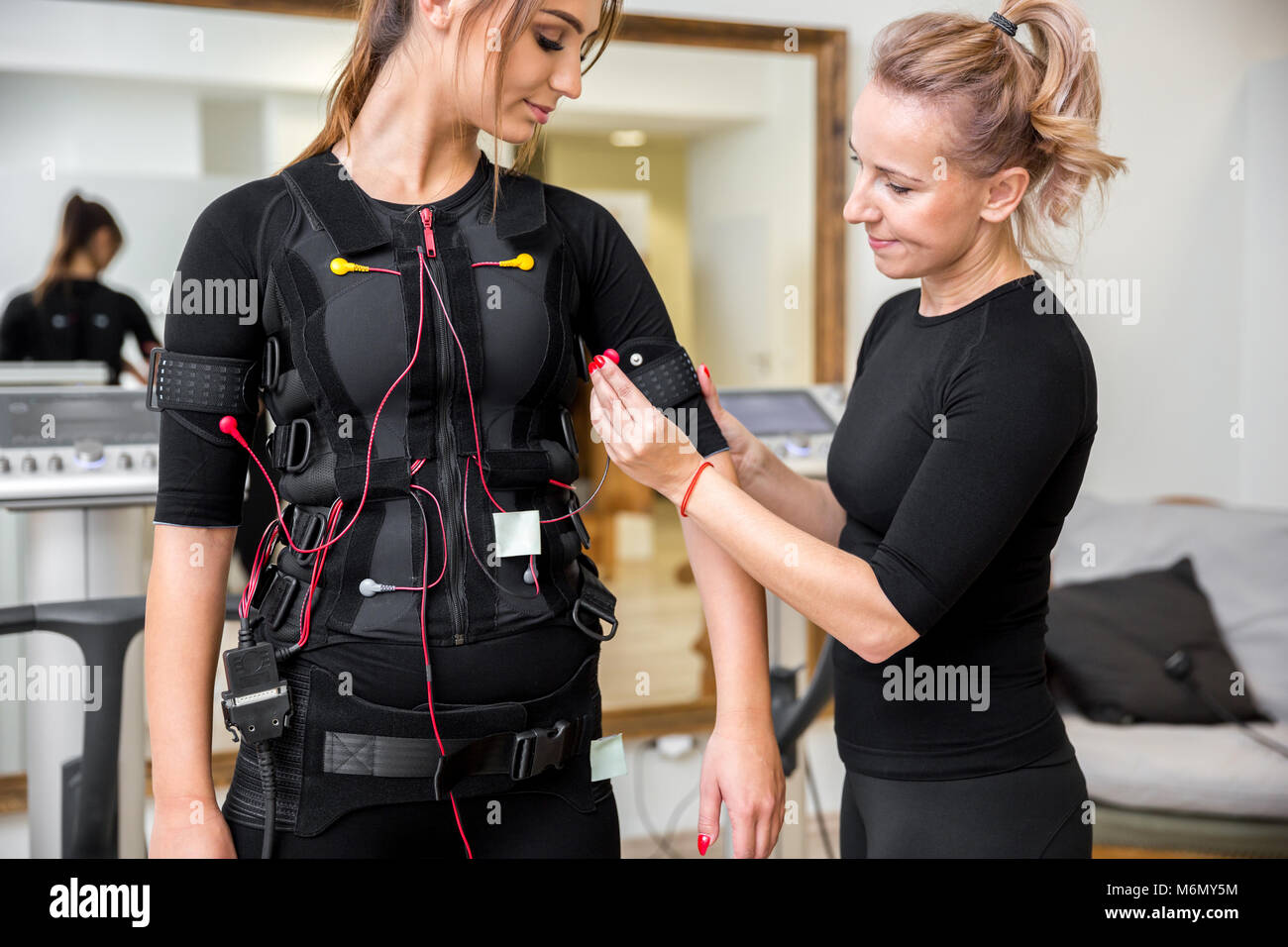 Portrait of personal trainer placing ems diodes on young woman - Stock Image