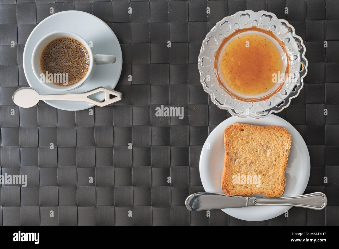 coffee cup and saucer slice biscuit and jam with mat placemat synthetic material shot from above breakfast concept - Stock Image