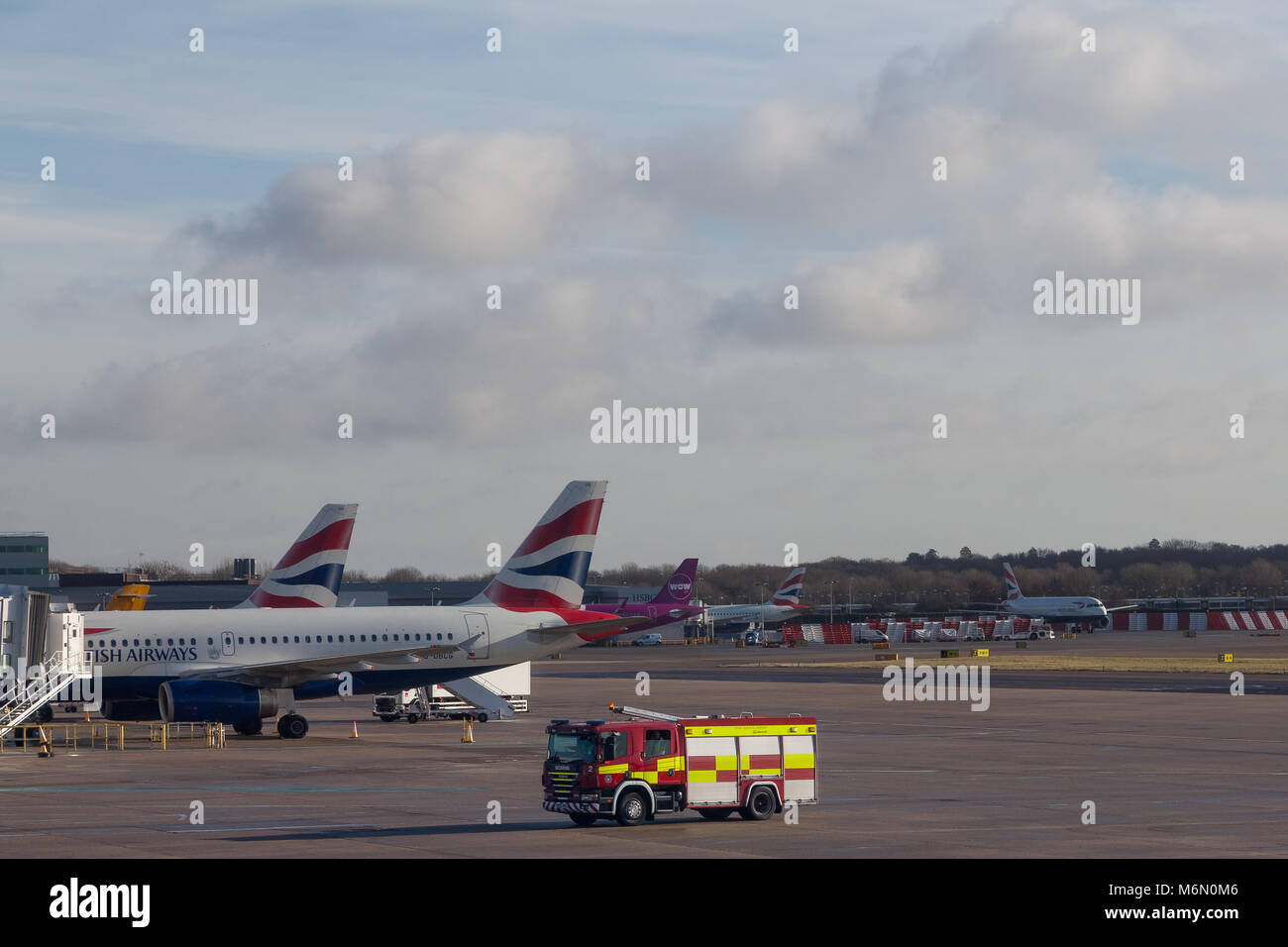 A fire engine in front of British Airways airliners at Heathrow Airport, London, UK. Wednesday January 10th 2018 - Stock Image