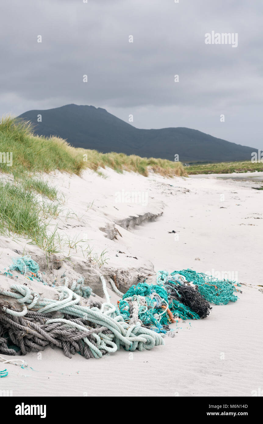 Fishing ropes and nets discarded and entangled in the beach and sand dunes on Howmore beach, South Uist, Outer Hebrides, - Stock Image