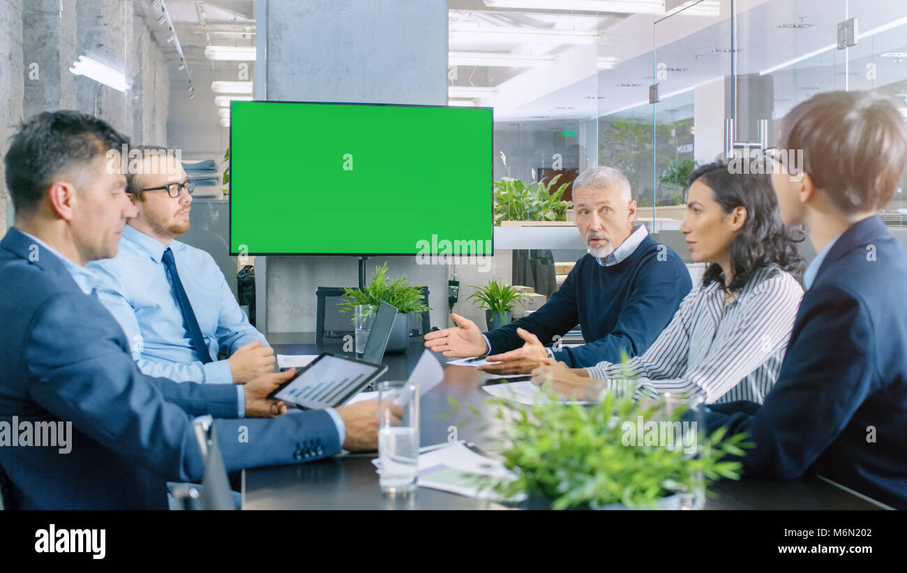 Diverse Group of Successful Business People in the Conference Room with  Green Screen Chroma Key TV on the Wall. - Stock Image
