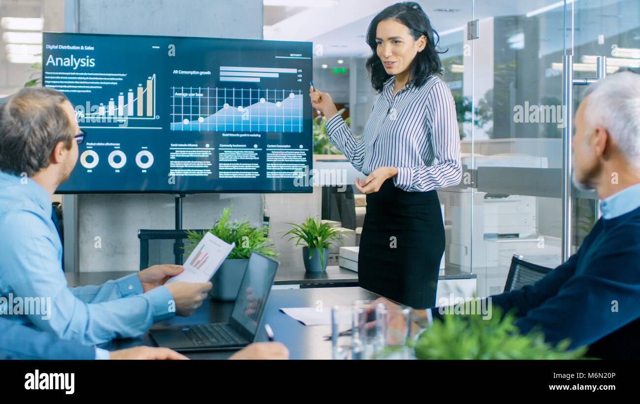 Beautiful Businesswoman Gives Report/ Presentation to Her Business Colleagues in the Conference Room, She Shows - Stock Image