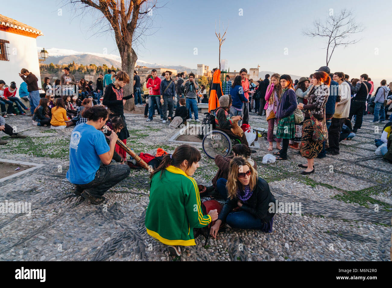 Granada, Andalusia, Spain. A crowd of tourists and young locals alike gathers at sunset in the San Nicolas lookout - Stock Image