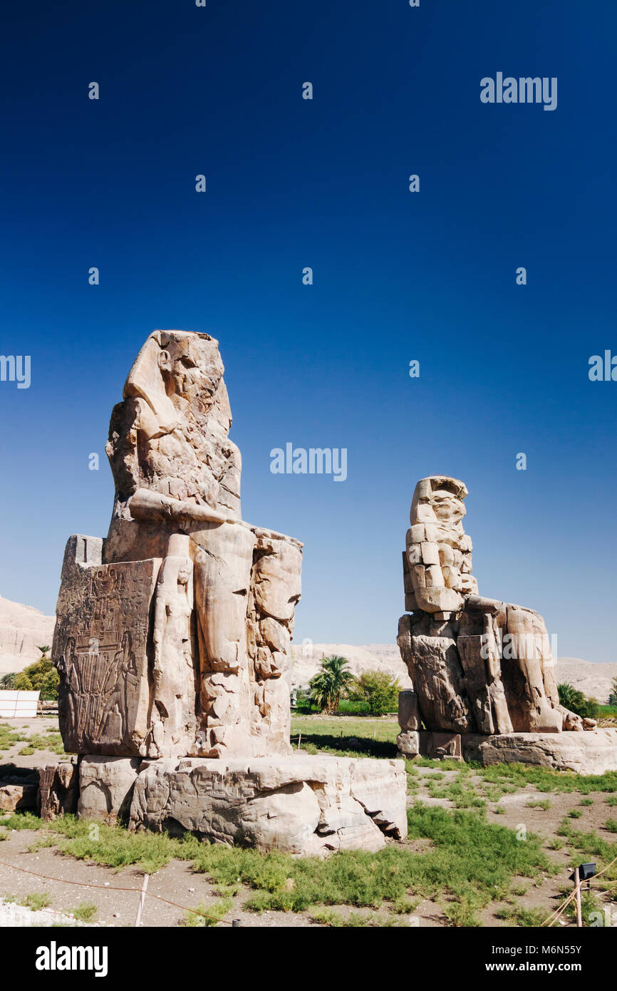 Luxor, Egypt. Colossi of Memnon,  two massive stone statues of the Pharaoh Amenhotep III, who reigned in Egypt during - Stock Image