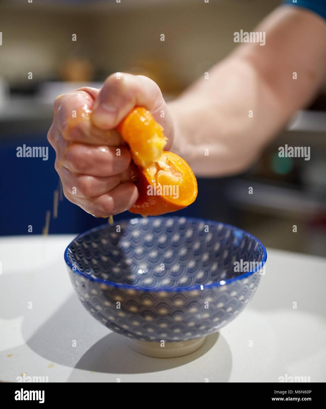 Man's hand furiously squashing an orange into a bowl - Stock Image