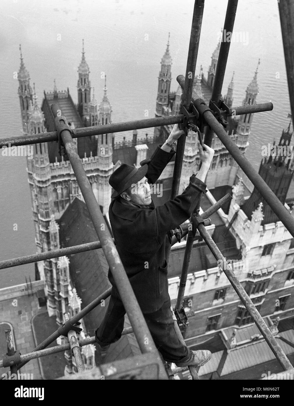 Construction worker erecting scaffolding on the 'Big Ben' clock tower on the Houses of Parliament also called - Stock Image