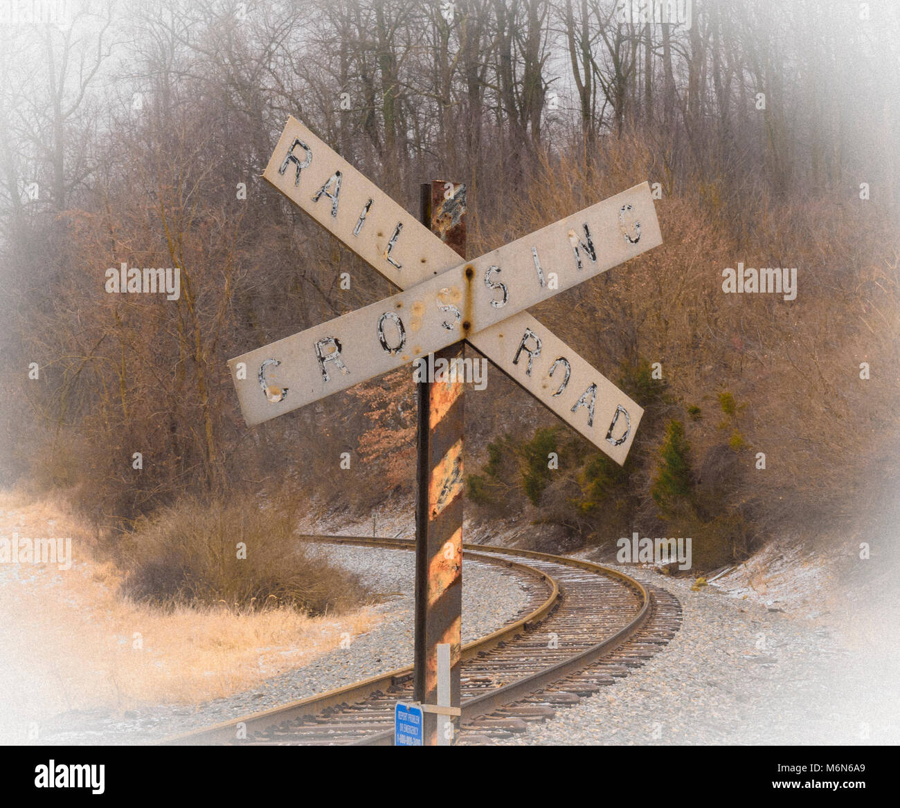 A vintage RR crossing sign located along side for a curve in the railroad tracks in eht winter. Vignetting effect - Stock Image