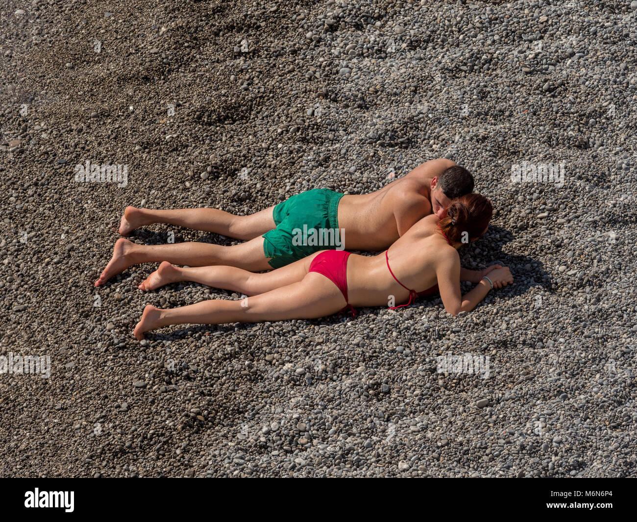 Young couple sunbathing on beach - Stock Image