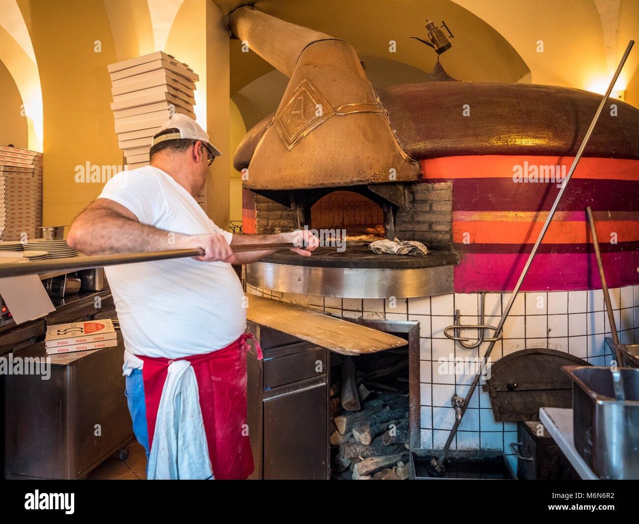 Pizza chef working with traditional Pizza oven - Stock Image