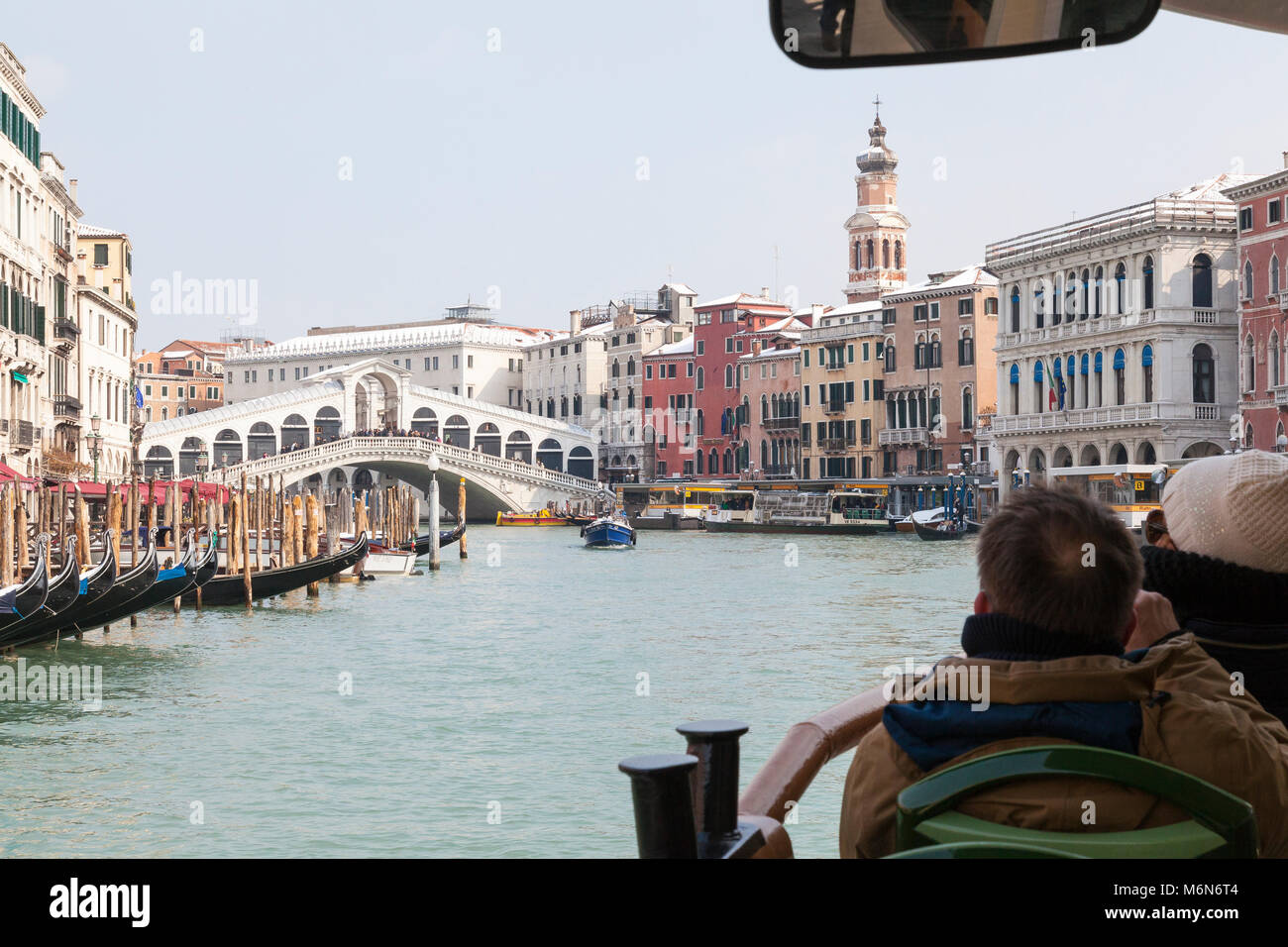 Tourists travelling on a vaporetto on the Grand Canal approaching the Rialto Bridge in winter with light snow on - Stock Image