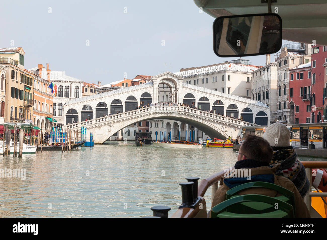 Tourists on a Vaporetto travelling up the Grand Canal, Rialto Bridge, Venice, Italy in winter with snow on the roofs, - Stock Image