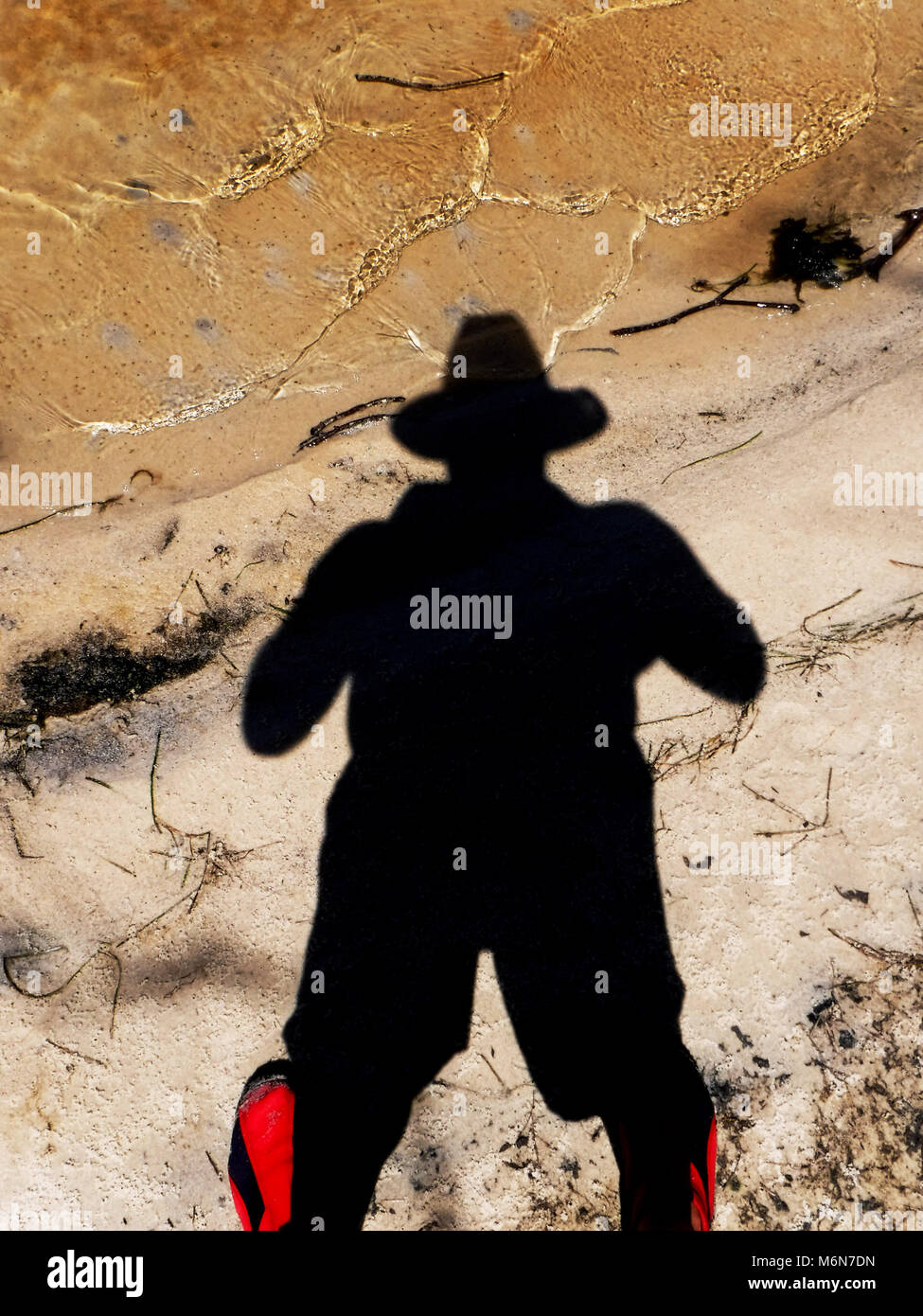 Dark shadow of man with hat against sand and water - Stock Image