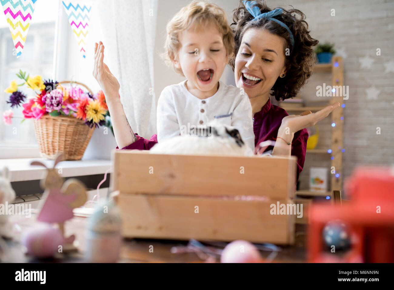 Young Mother Presenting Easter Bunny to Son - Stock Image