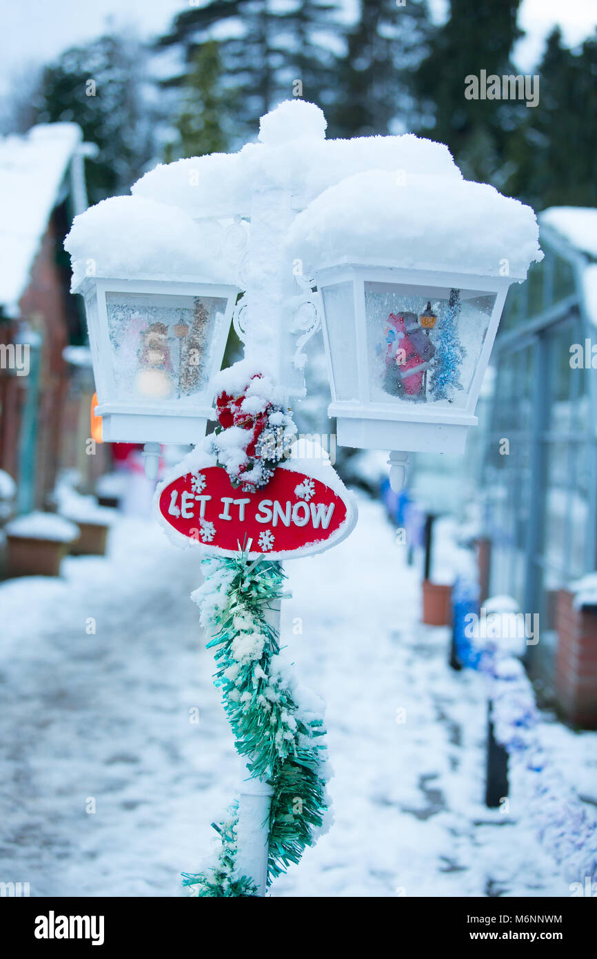 Portrait close up of a snow-covered Christmas garden decoration, stating 'Let it snow'. - Stock Image