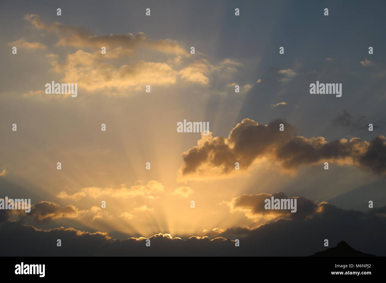 golden rays of early morning sunrise light bursting through clouds - Stock Image
