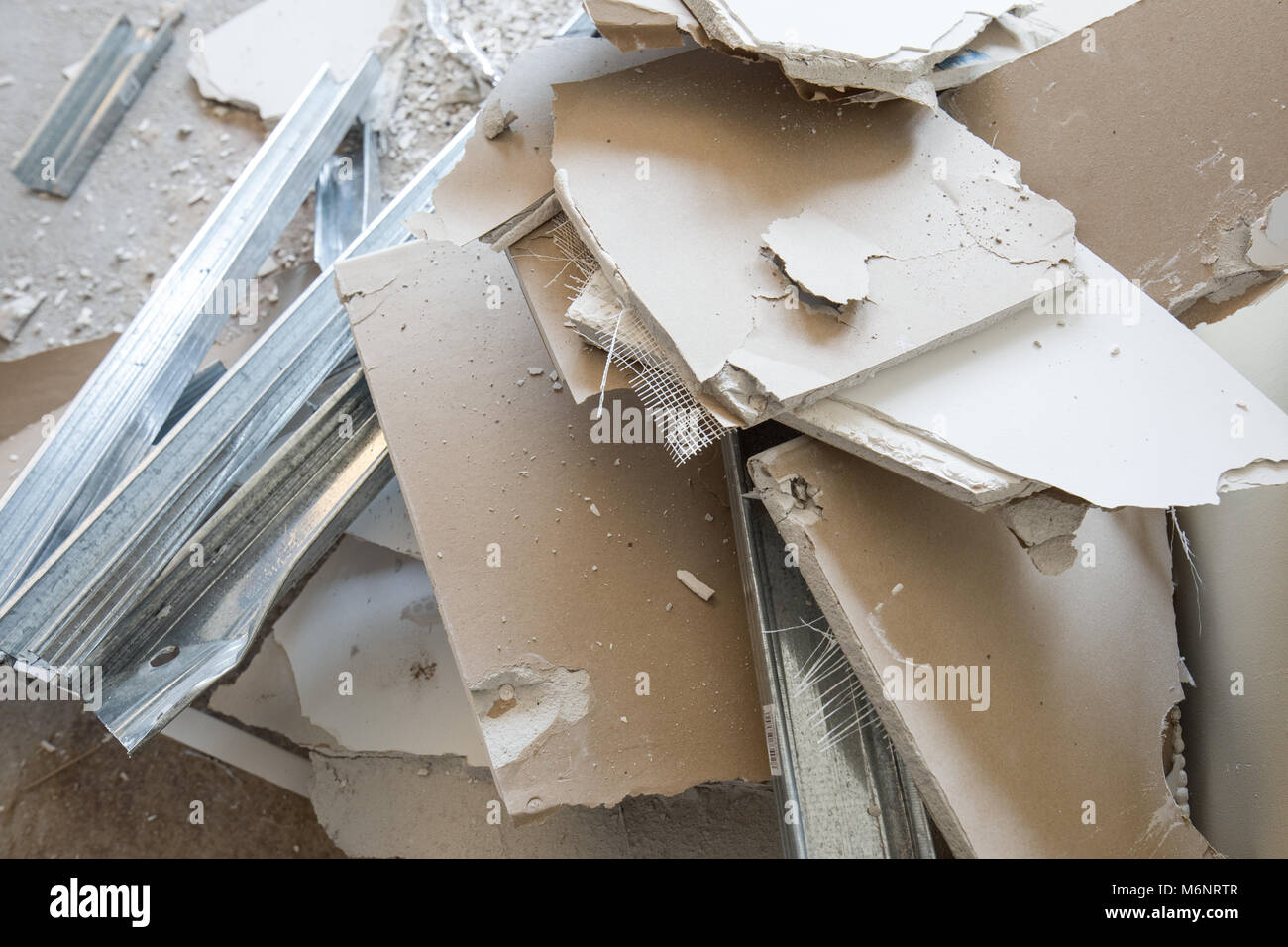 Heaps of rubble, pices of gypsum plasterboard and mounting rails. Mess  and demolition, ruins, renovation works - Stock Image