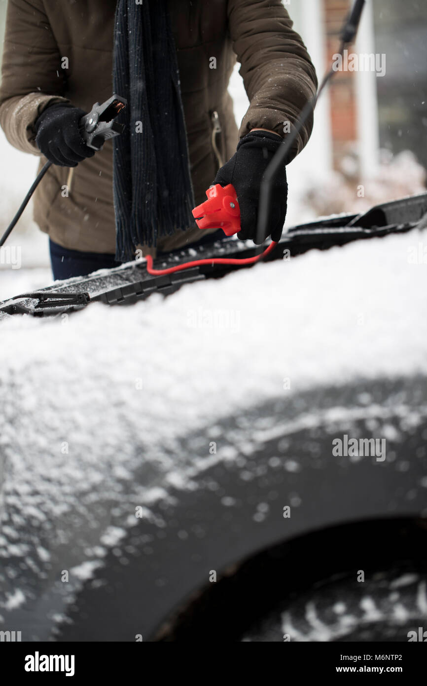 Woman Using Jumper Cables On Car Battery On Snowy Day - Stock Image