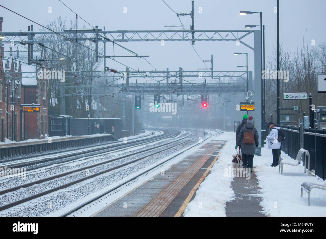 Passengers wait on a platform at an Atherstone train Station covered in snow. The snow has been cleared to make - Stock Image
