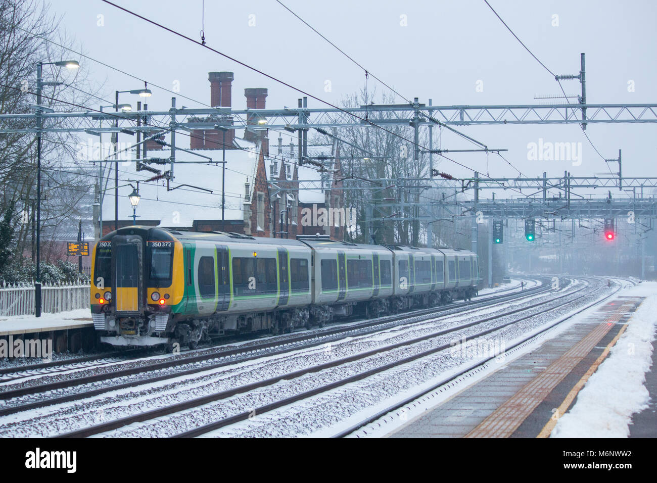 A south bound West Midlands Railway train departing Atherstone train Station covered in snow - Stock Image