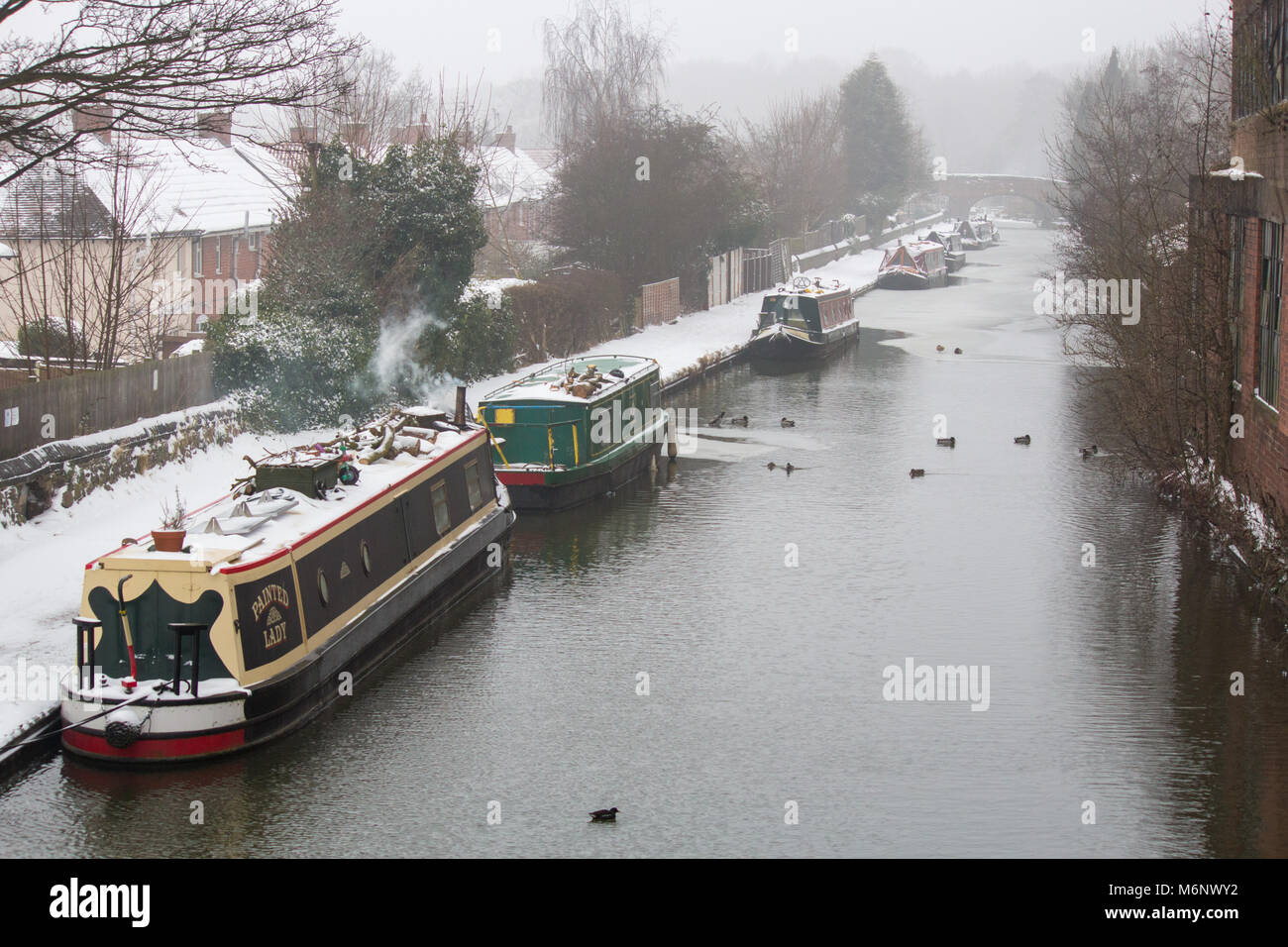 Canal boats, barges, narrow boats covered in snow on the Coventry canal, near Atherstone, Warwickshire - Stock Image