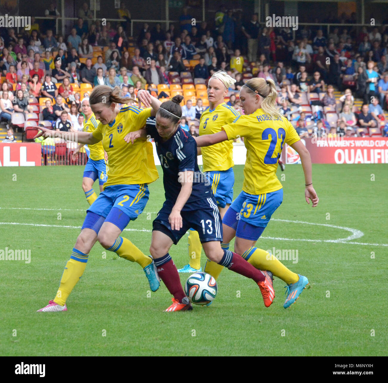 MOTHERWELL, SCOTLAND - JUNE 14th 2014: Scotland's Jane Ross trying to keep the ball from three Swedish players. Stock Photo