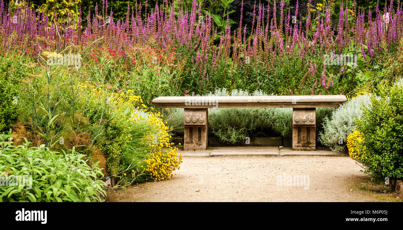 Stone bench in the exuberantly planted kitchen garden of Hardwick Hall in Derbyshire UK - Stock Image