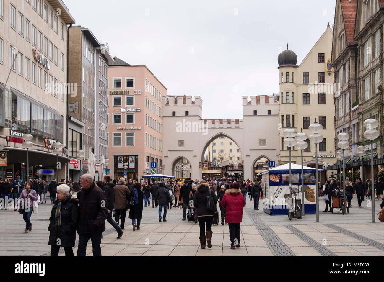 Busy street scene on pedestrianised shopping precinct in old town city centre at Karlstor gate on Neuhauser Strasse, - Stock Image