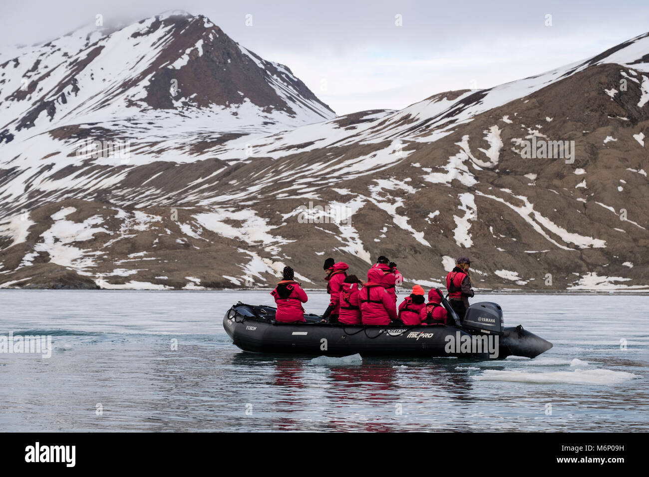 G Expedition cruise passengers in a Zodiac dinghy watching for wildlife off coast of Spitsbergen island, Svalbard, - Stock Image