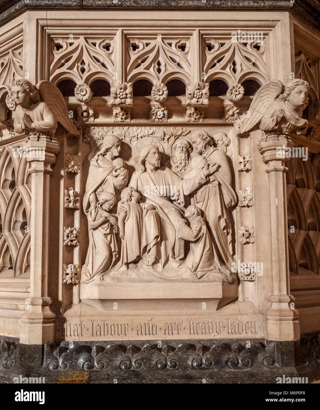Finely carved stone pulpit of Tewkesbury Abbey showing scenes from the life of Christ here Jesus blessing adoring - Stock Image