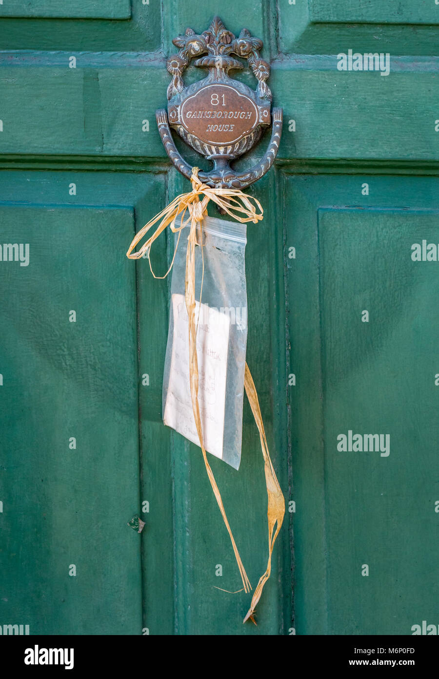 Charming hand written note tied up with raffia to the postman on a door knocker in a small town in central England - Stock Image