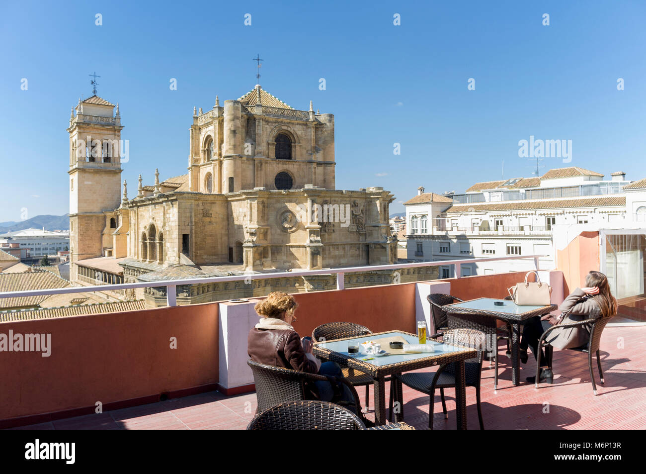 Women relaxing at the rooftop bar of Los Jeronimos hotel opposite the Real Monasterio de San Jerónimo. Granada, - Stock Image