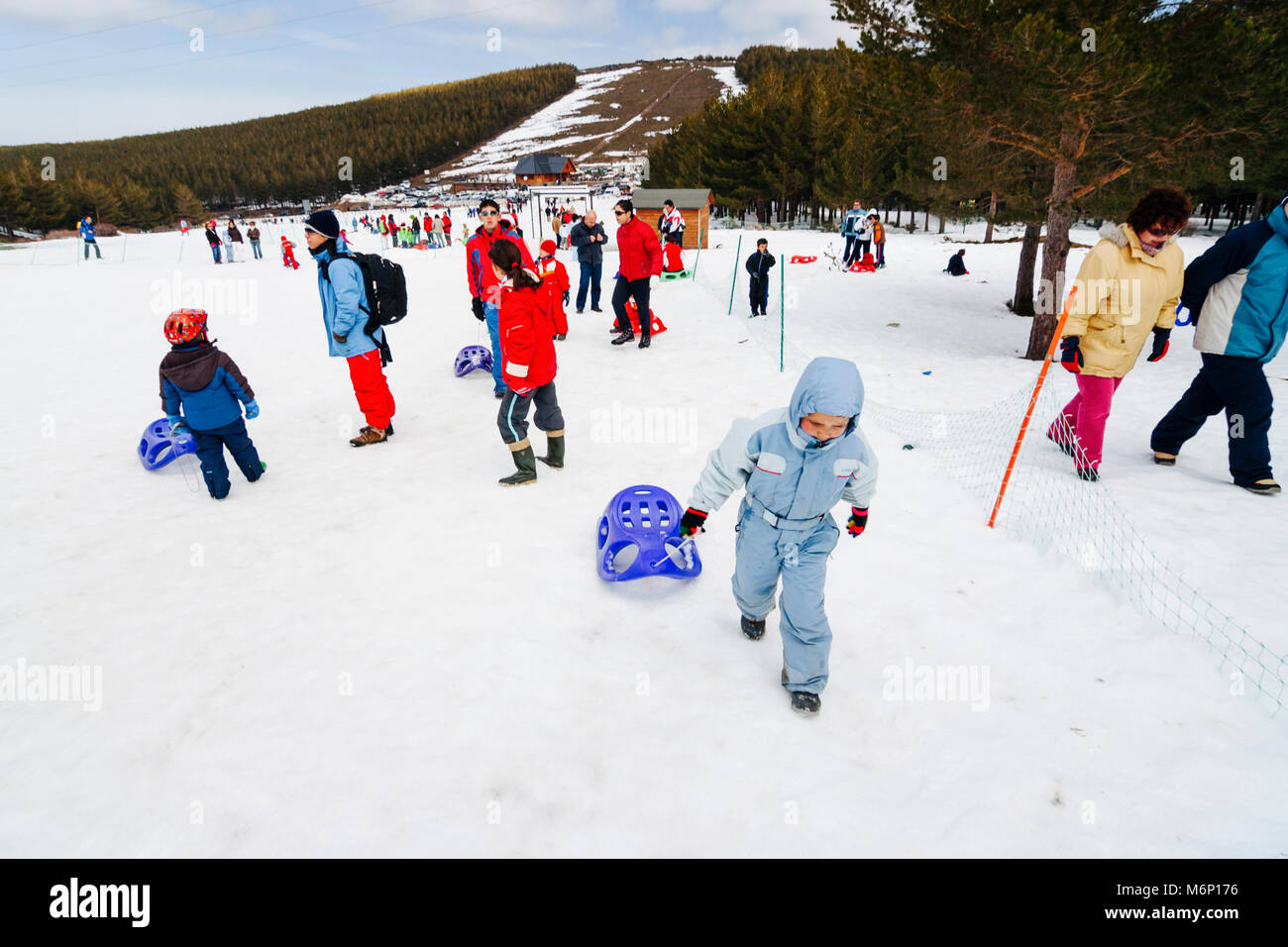 A child in ski suit is pushing a sledge on a snow-covered field at Puerto de la Ragua Ski resort in Sierra Nevada, Stock Photo
